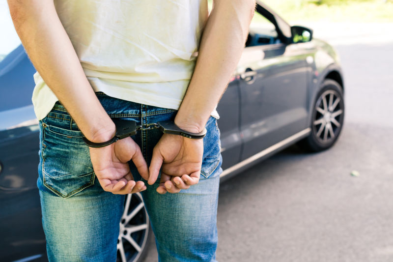 an offender standing in handcuffs near the car. Concept of arrest the driver, violation of rules and drinking alcohol while driving the car